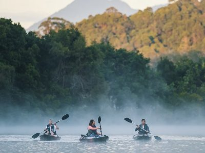 Friends enjoying an early morning kayak tour on Tweed River with scenic views of Mount Warning.